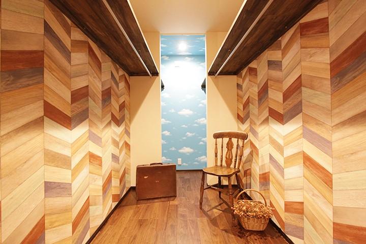 木目タイルの壁の奥に明るい空色のクロスを敷いた空間がアクセントになり広さを感じる空間を演出。