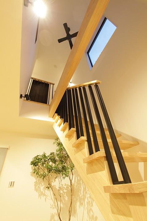 2階へ続く吹き抜けの階段の骨組みにダークカラーを使用してアクセントに。階段に沿って視線を上げると天井に骨組みと同じダークカラーのシーリングファンが目に入ります。