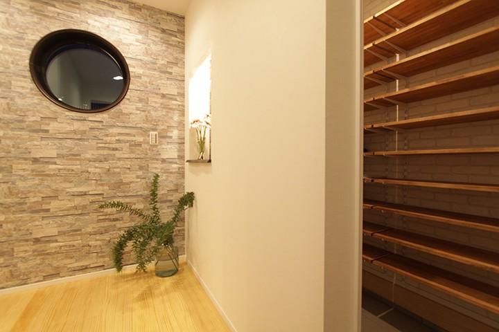玄関からつながるシューズクローク。壁の一部を区切ったレンガタイルの飾り棚を設けてアクセントに。