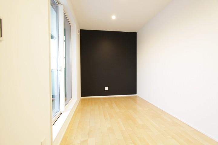 一面のみ色を入れた洋室。広い窓からは明るい光と風が入ります。